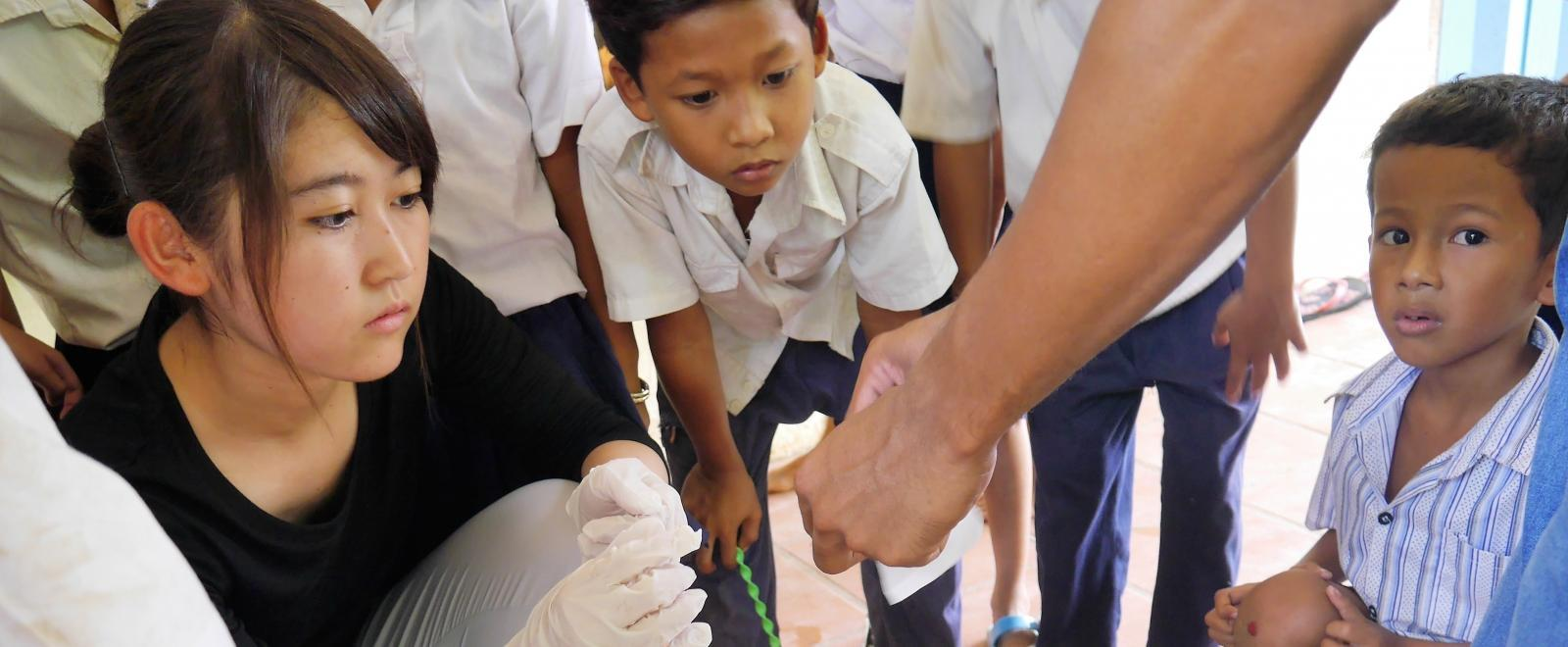 A female intern is pictured taking part in testing blood sugar levels whilst on her public health internship in Cambodia.